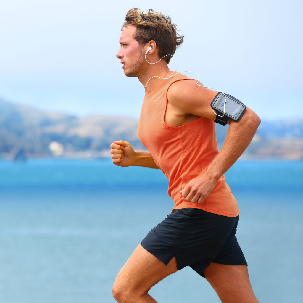 male runner exercising in summer while listening to music and running by water