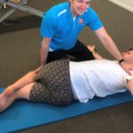 physiotherapist helping young male with back stretch exercise